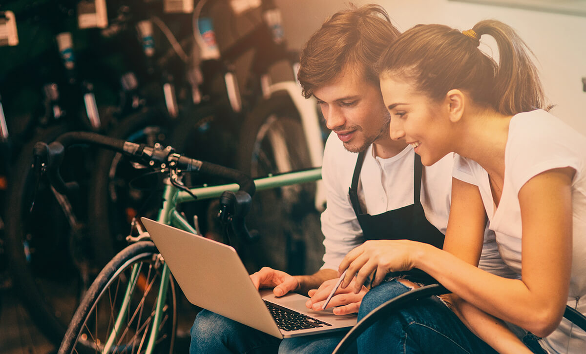 A young man and woman sitting inside a bikeshop are smiling while looking at the screen on a laptop. © iStock.com/filadendron